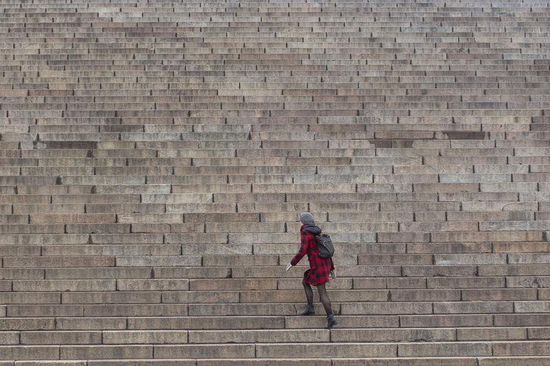 Full length of man walking against brick wall