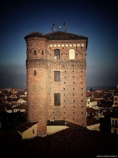 looking from a crack Italy Piedmont Fossano Tourism Travel History Stone Wall Defence Tower Architecture Built Structure Building Exterior No People History Travel Destinations Sky Clear Sky Outdoors Day City Cityscape