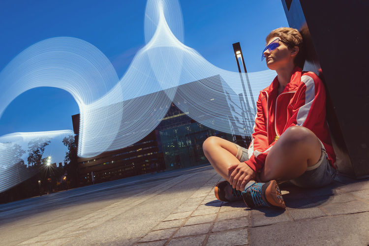 Portrait of young woman sitting outdoor on a ground on a long exposure, freeze light concept