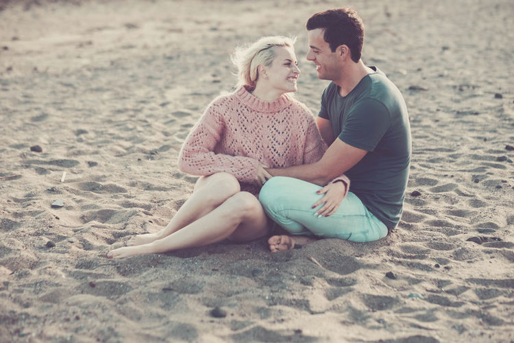 Smiling young couple sitting on sand at beach