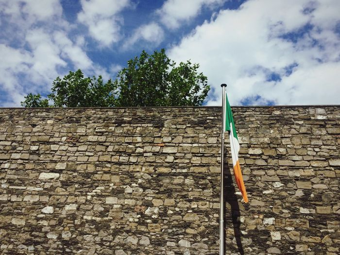 A wall and flag in Ireland KilmainhamGaol Gaol Jail Dublin, Ireland Dublin Irish Flag Ireland🍀 Irish Ireland Sky Cloud - Sky Plant Nature Day Tree No People Built Structure Outdoors Pole Wall Low Angle View Wall - Building Feature