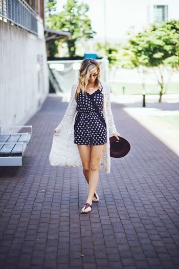 Portrait of young woman standing on footpath