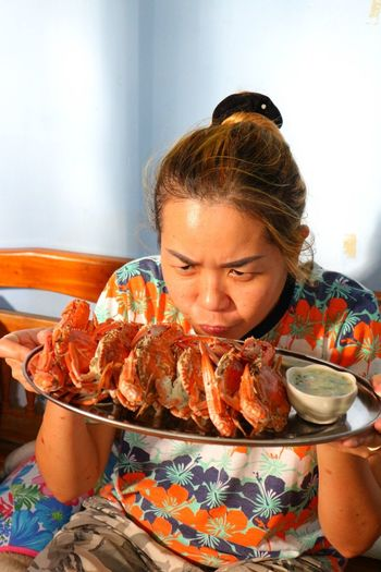 Woman holding crabs on bed at home