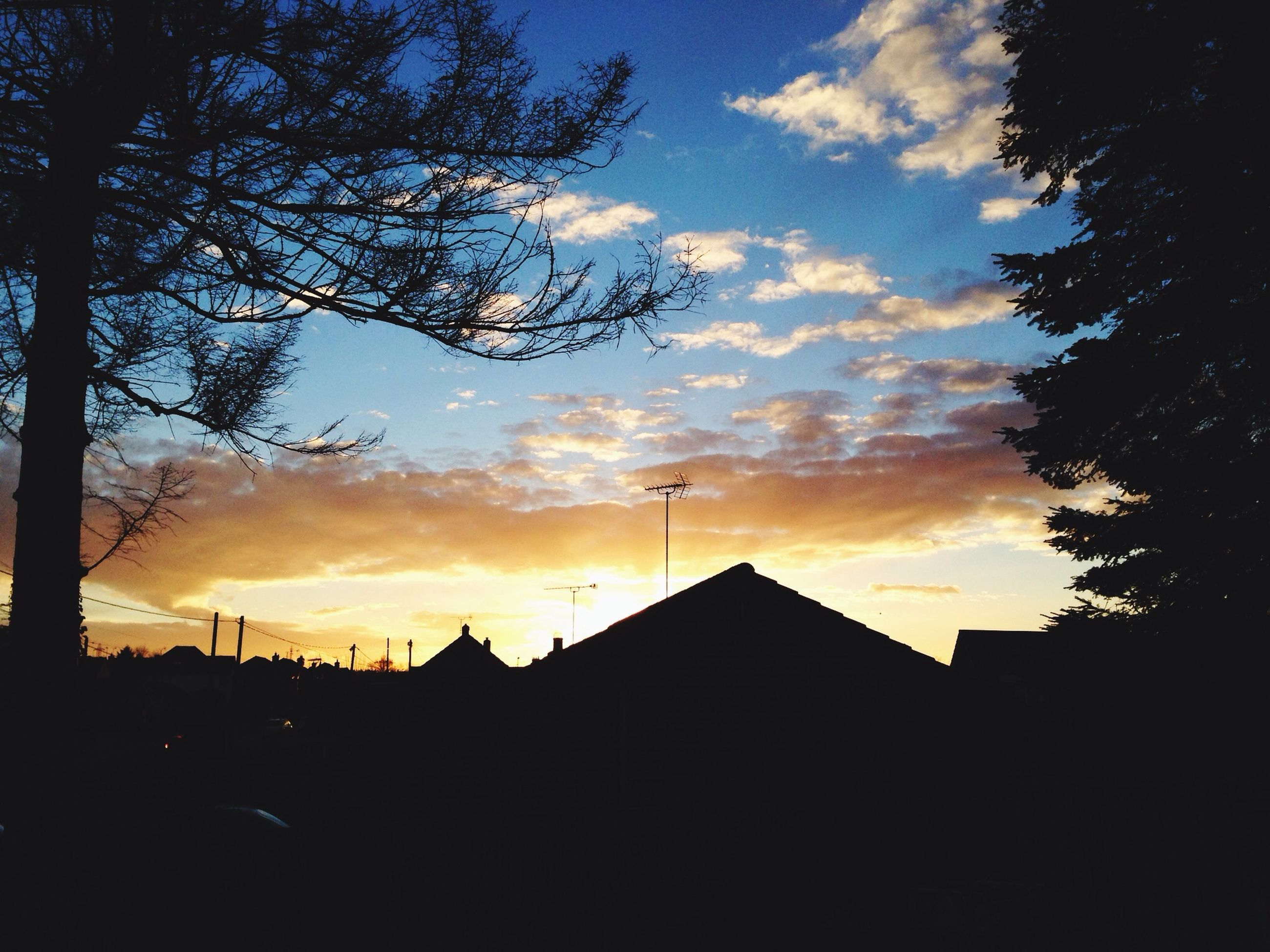 sunset, building exterior, silhouette, architecture, sky, built structure, orange color, tree, cloud - sky, house, low angle view, residential structure, cloud, residential building, beauty in nature, outdoors, city, nature, building, dramatic sky