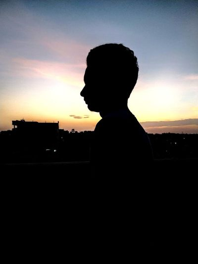 Side view of silhouette man standing against sky during sunset