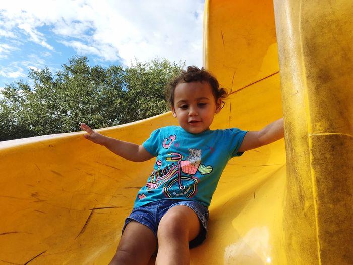 Low angle view of girl enjoying slide