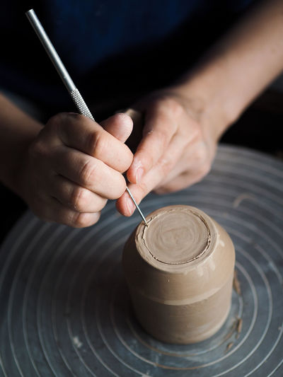 Midsection of woman making earthenware at workshop