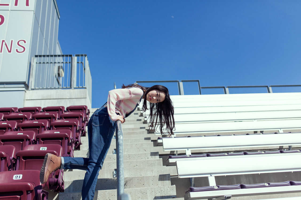 steps, built structure, real people, one person, outdoors, architecture, building exterior, day, railing, young adult, clear sky, lifestyles, staircase, full length, leisure activity, casual clothing, blue, young women, sky, beautiful woman, people
