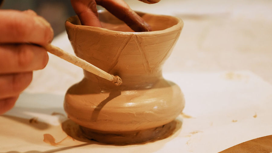Cropped Hands Of Craftsperson Making Clay Product In Pottery Workshop