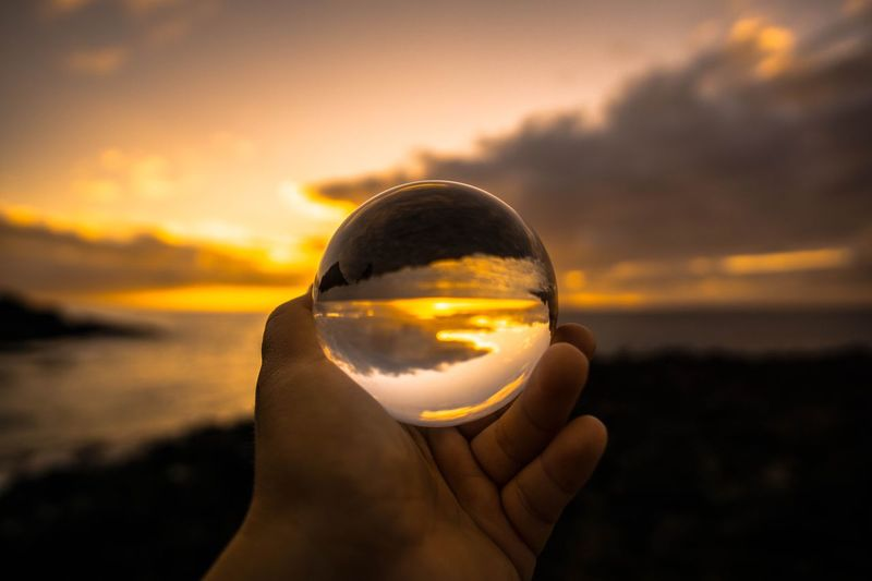 Close-up of hand holding crystal ball against sunset sky