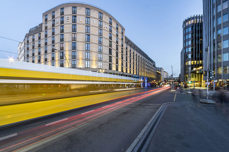 Blurred motion of light trails on road amidst buildings in city