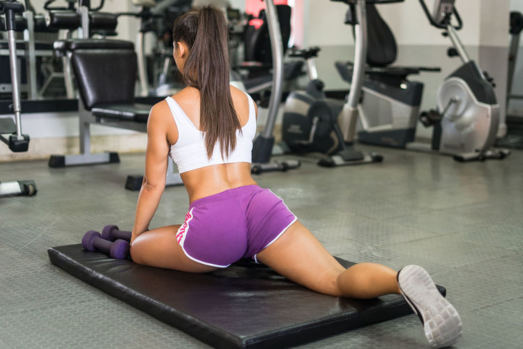 Adult Body Conscious Clothing Effort Equipment Exercise Equipment Exercising Full Length Gym Health Club Healthy Lifestyle Indoors  Lifestyles Muscular Build One Person Rear View Sport Sports Clothing Sports Training Strength Vitality Weight Weight Training  Wellbeing Women