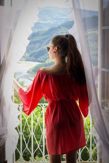 Anita/5 Back Elégance Ponytail Balcony Beautiful Woman Beauty Brown Hair Casual Clothing Clothing Contemplation Curtains Day Hairstyle Looking Looking Away One Person Red Satin Dress Standing Sunglasses Three Quarter Length Window Women Young Adult Young Women The Fashion Photographer - 2018 EyeEm Awards