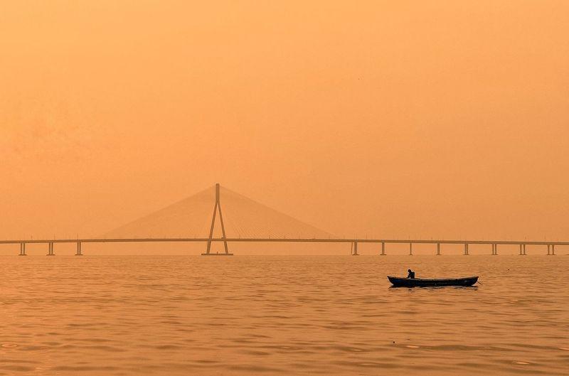 Scenic view of suspension bridge over sea against sky during sunset