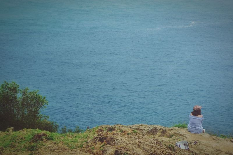 Rear View Of Woman Looking At Sea While Sitting On Land