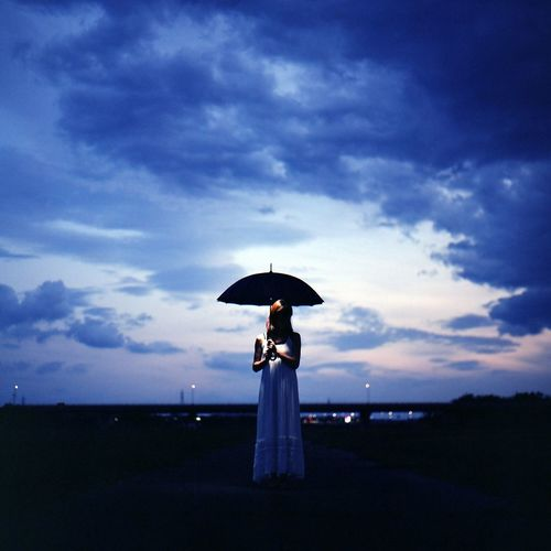 Woman Standing With Umbrella Against Blue Sky