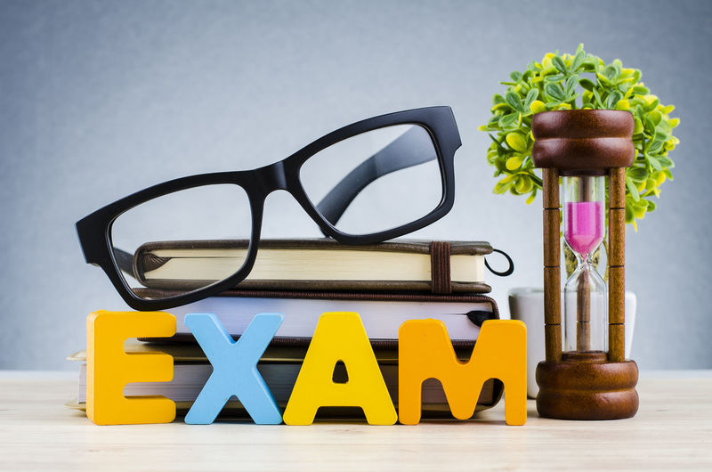 Education and time management concept, word EXAM over hourglass, and spectacles on stacking book Still Life Indoors  Glasses Table No People Eyeglasses  Close-up Studio Shot Yellow Wood - Material Plant Text Multi Colored Transparent Nature Capital Letter Education Flower Focus On Foreground Western Script Personal Accessory