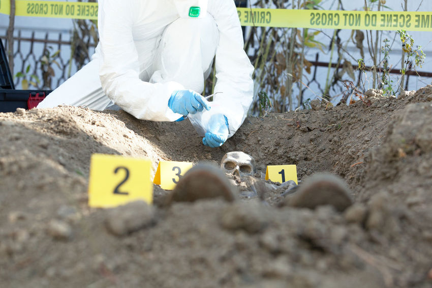 Forensic science expert collecting evidence at a crime scene. Police investigation Forensic Forensics Investigation Investigator Evidence Marker Skeleton Body Part Grave Murder Death Crime Crime Scene Police WorkWear Skull Evidence Dna Homicide Massachusetts Scene Law Enforcement Exhumation Criminology Morbid