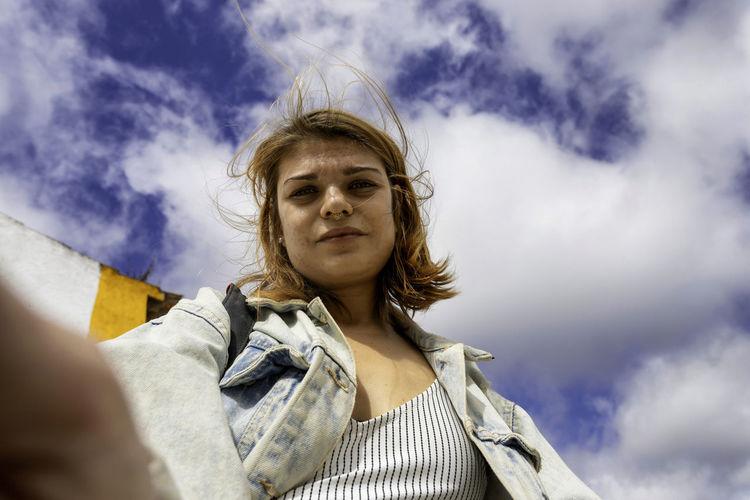 Portrait of woman doing selfie against sky