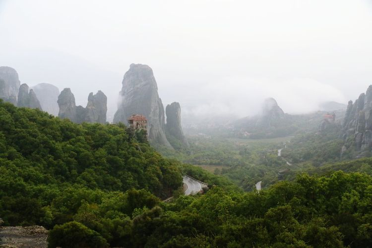 Landscape With Rock Formation And Trees In Fog