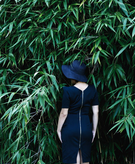 Rear view of woman wearing hat standing against plants