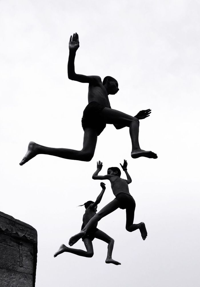 LOW ANGLE VIEW OF MAN JUMPING WITH ARMS RAISED AGAINST SKY