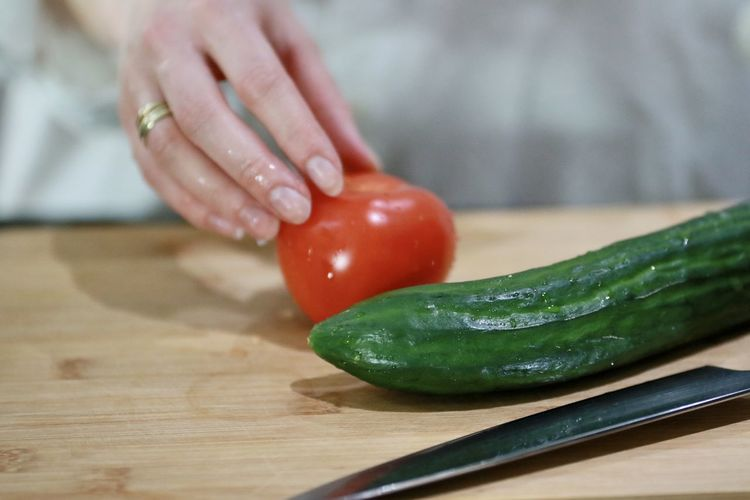 Close-up of hand holding tomato on cutting board