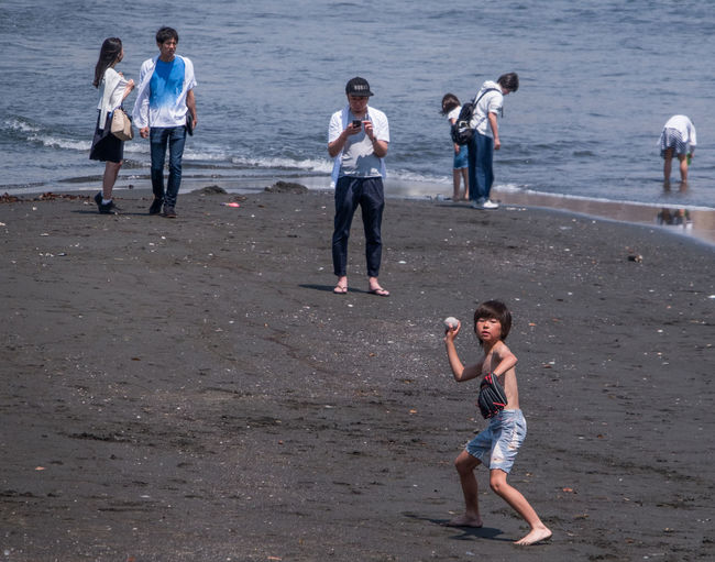 Full length of friends standing on beach