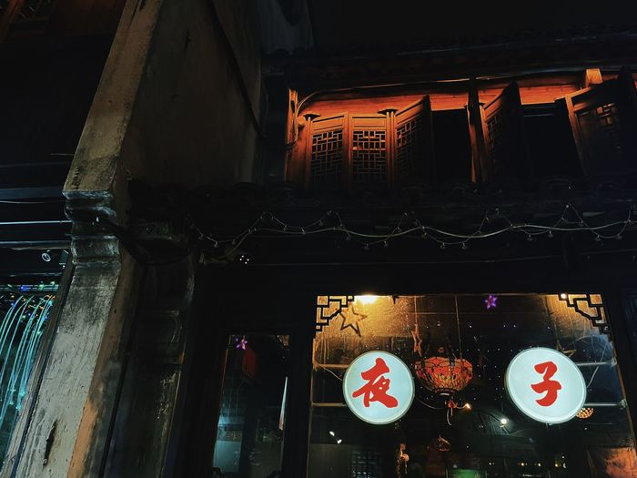 Low angle view of illuminated lanterns hanging on building at night