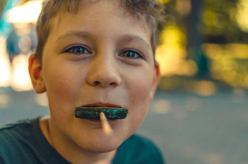 Close-up portrait of boy having lollipop