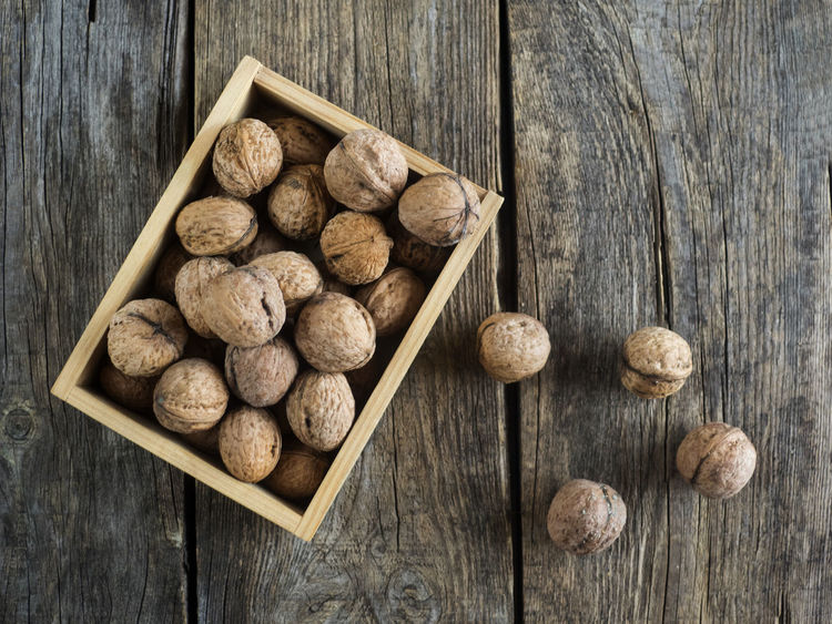 walnuts in a wooden box on an old weathered wooden table Box Weathered Wood Background Close-up Day Directly Above Directly Abowe Food And Drink Freshness High Angel View High Angle View Indoors  No People Old Studio Shot Table Walnuts Wood - Material Wood Grain Wooden