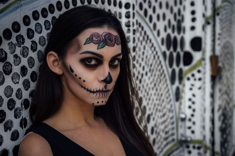 Close-up portrait of woman with spooky halloween make-up against wall