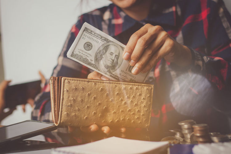 Midsection of man putting money in purse