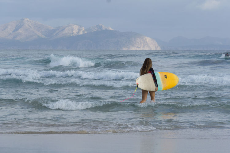 Woman With Surfboard Walking In Sea Against Sky