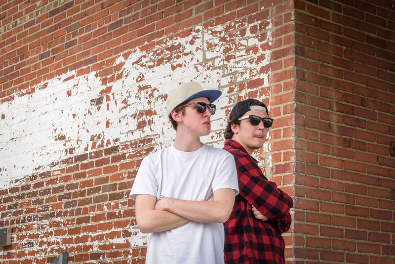two young men thuggin back to back against brick wall wearing snapback hats and sunglasses Acting Silly Back To Back Baseball Cap Boys Boys Will Be Boys Brick Wall Buffalo Plaid Day Friendship Men Outdoors People Real People Snapback Standing Style Sunglasses Sunglasses :) Teens Thuggin Togetherness Two People Urban Young Adult Young Men