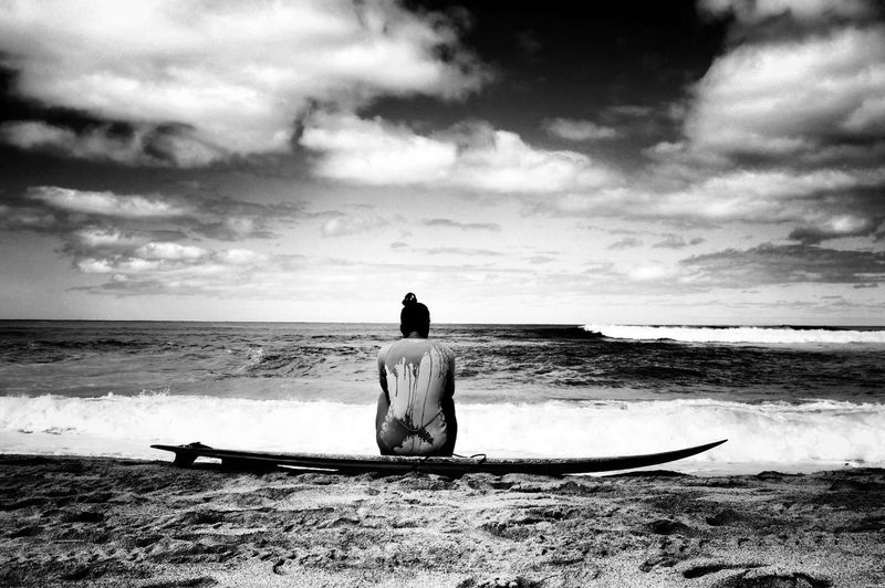 Rear view of woman sitting on surfboard at beach