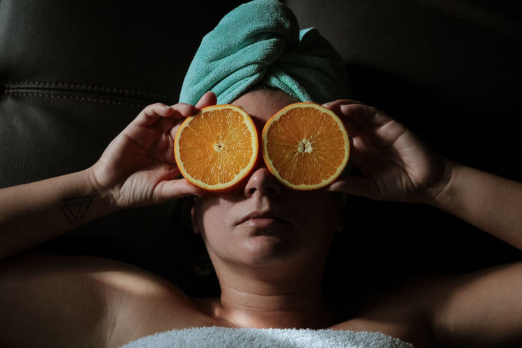Midsection of woman holding orange slices