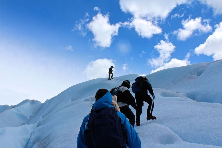 Low angle view of people climbing on snowcapped mountain against sky