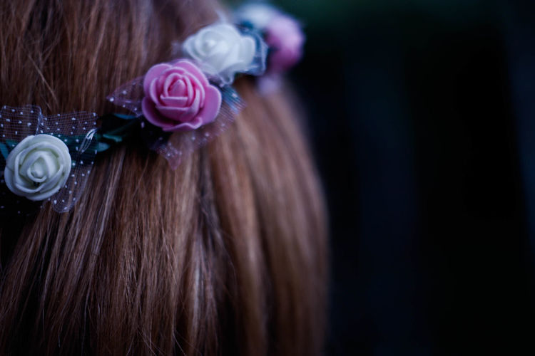 Close-up of woman wearing flowers on hair against black background