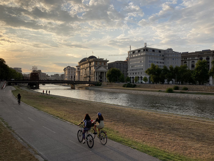 People riding bicycle by river in city against sky