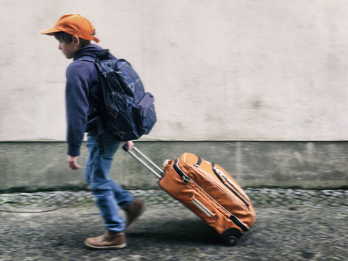Side View Of Boy With Luggage Walking On Footpath