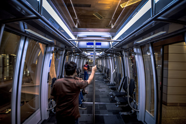 Rear view of man holding pole while traveling in metro train