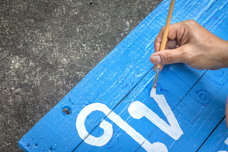 Writing signs board with a brush of watercolors on cement floor background. Painting on wooden board in thai language for advertising. Blue Hand One Person Human Hand Human Body Part High Angle View Holding Day Close-up Wood - Material Text Outdoors Paint Table Creativity Art And Craft Body Part Real People Finger Art And Craft Equipment Paint Painting Brush Wooden Post Board