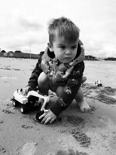 Cute boy sitting on beach
