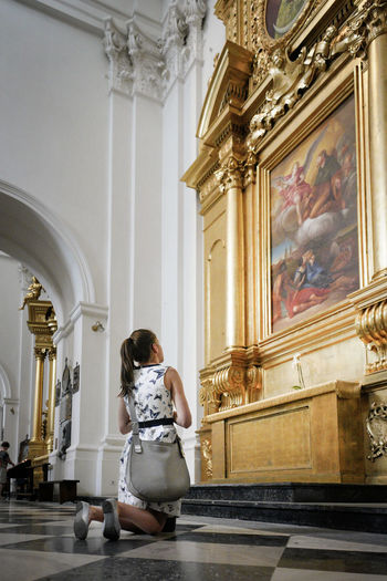 A young woman prays inside the Holy Cross Church, Kościół Świętego Krzyż Poland June 2018 Church Gold Jesus Pray Adult Architecture Belief Building Built Structure Full Length Gold Colored Hairstyle Indoors  Kneeling Kneeling Down One Person Painting Place Of Worship Praying Real People Rear View Religion Spirituality Women Young Women