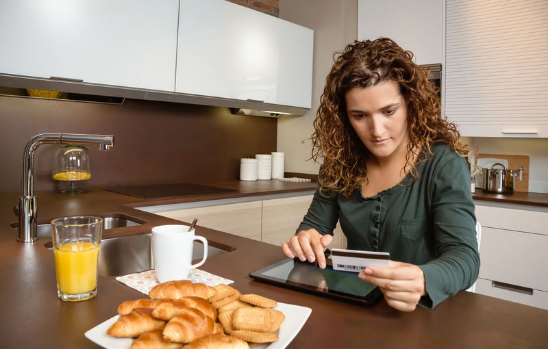 Portrait of young woman with electronic tablet and credit card buying on internet. Online shopping concept. Single One Person Holding Interior Electronic Commerce Purchase Adult Leisure Paying Portrait Wireless Commerce Love Websurfing Female Caucasian Sitting Indoors  Young Ecommerce E-commerce Technology Buying People Smile Girl Weekend Coffee Cup Juice Orange Breakfast Lifestyle Happy Payment Shopping Internet Home Kitchen Woman Online  Credit Card Card Credit Pad Electronic Tablet