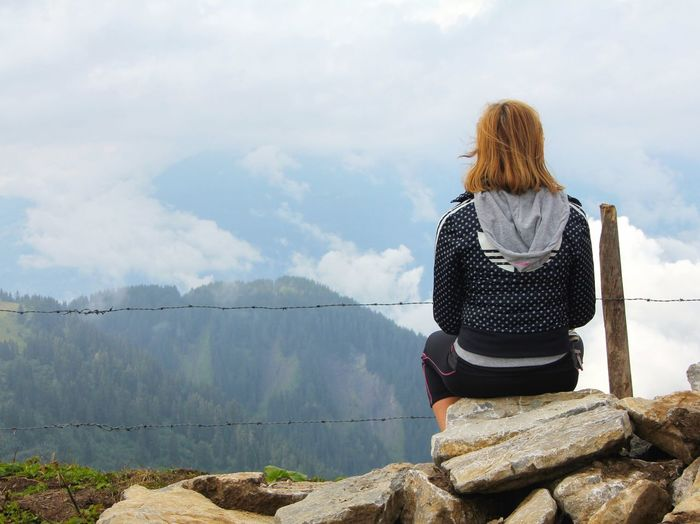 Rear view of woman sitting on rock against cloudy sky