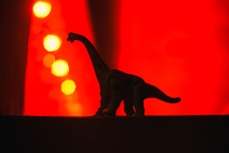 A dinosaur with red background Dinosour Toy Red Red Color Red Background Silhouette Yellow Circle Standing Vibrant Color Animal Representation Animal Silhouette Red Indoors  No People Mammal