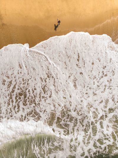 High angle view of man walking by surf on shore at beach