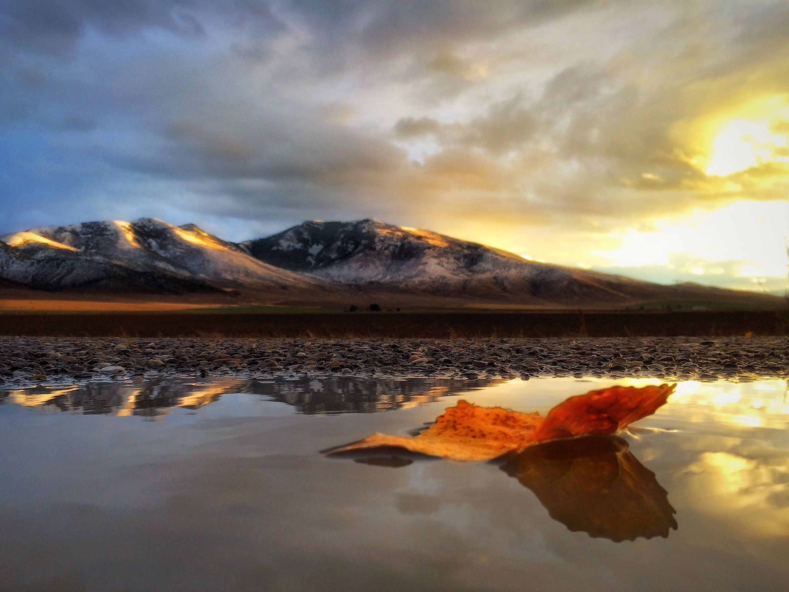 water, sky, cloud - sky, reflection, tranquility, lake, nature, tranquil scene, sunset, beauty in nature, scenics, cloudy, weather, season, cloud, cold temperature, winter, outdoors, mountain, orange color